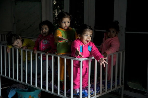 A group of girls stand in a crib at Unique Home.